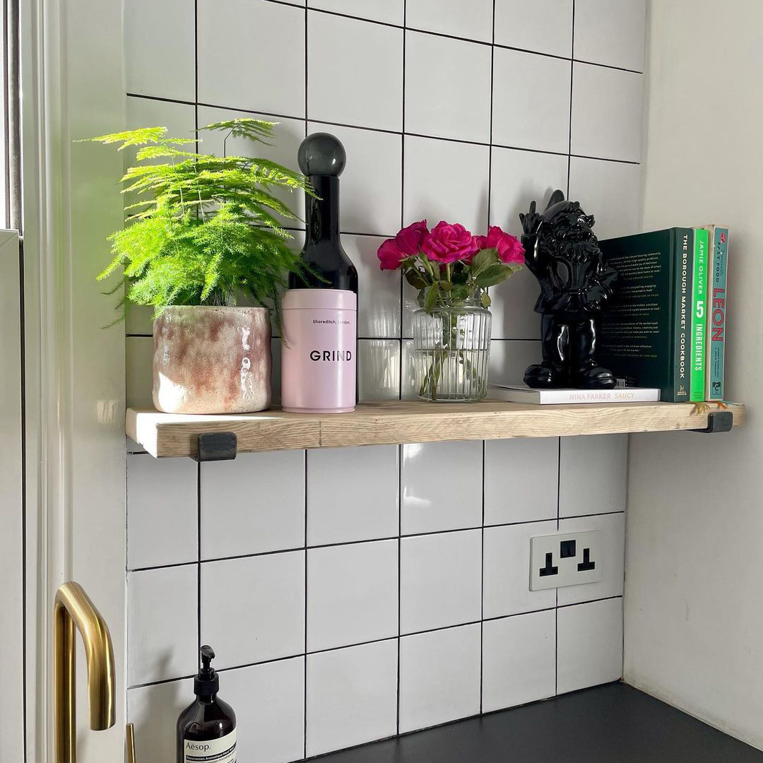 white and black double socket on white tiled wall in a kitchen