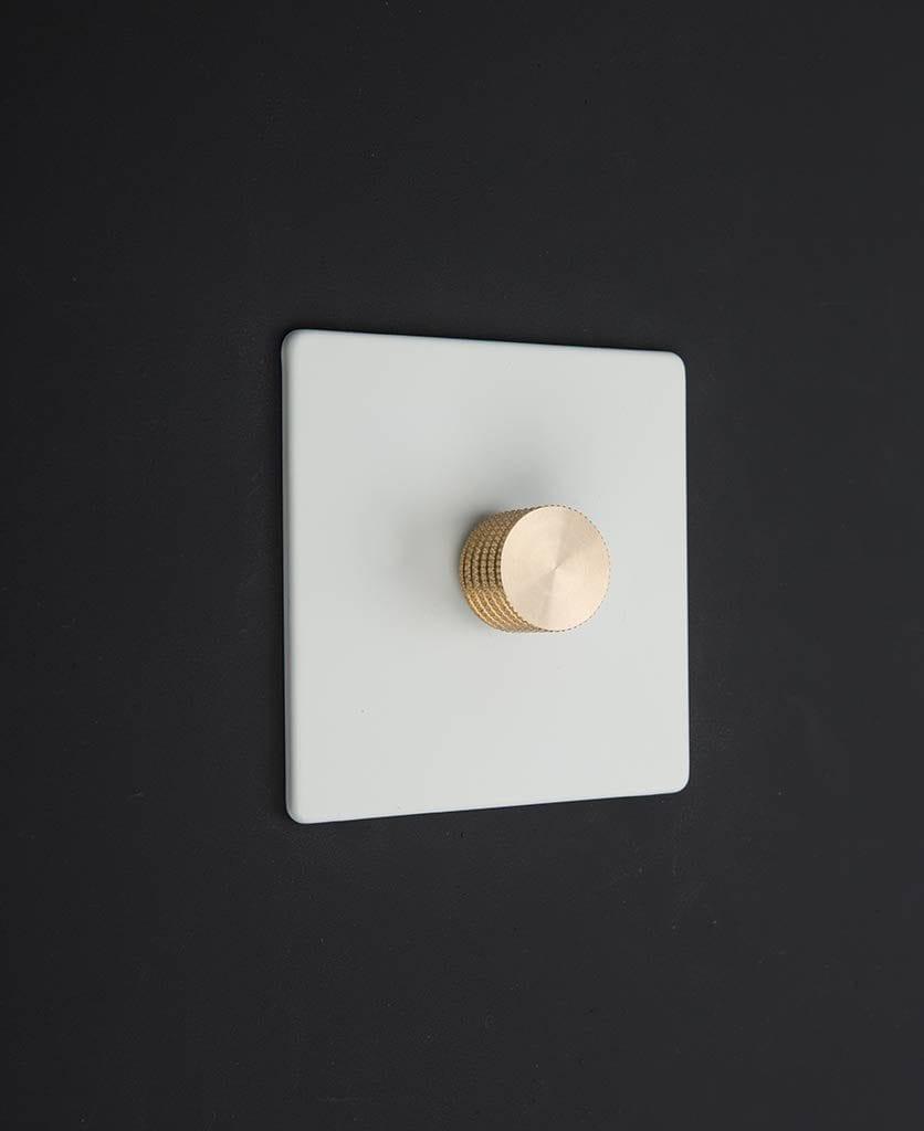 white & gold single dimmer against black background