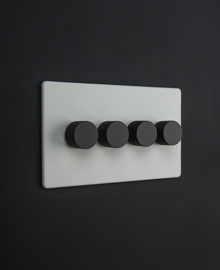white dimmer switch with four black knurled dimming knobs