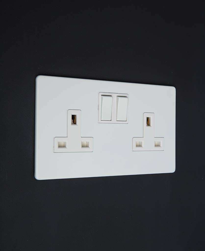 white plug sockets with white inserts against black background