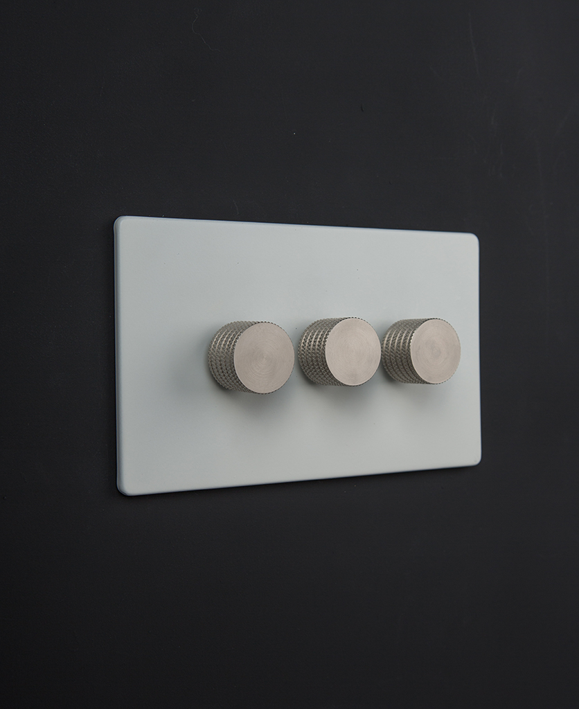 white triple dimmer switch with silver knurled knobs against black background