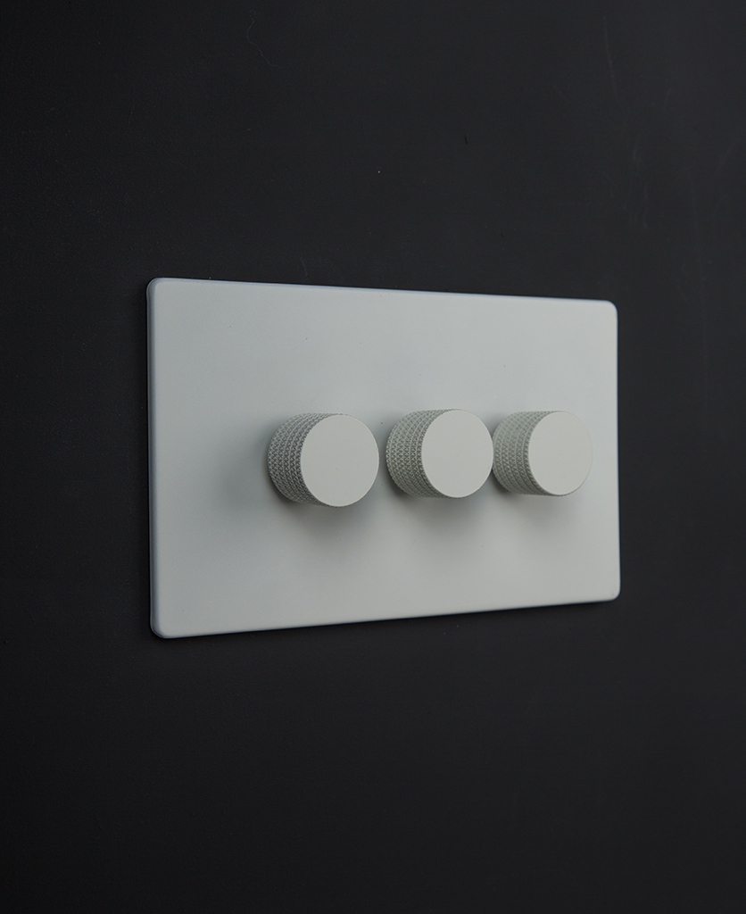 white triple dimmer switch with three white dimming knobs