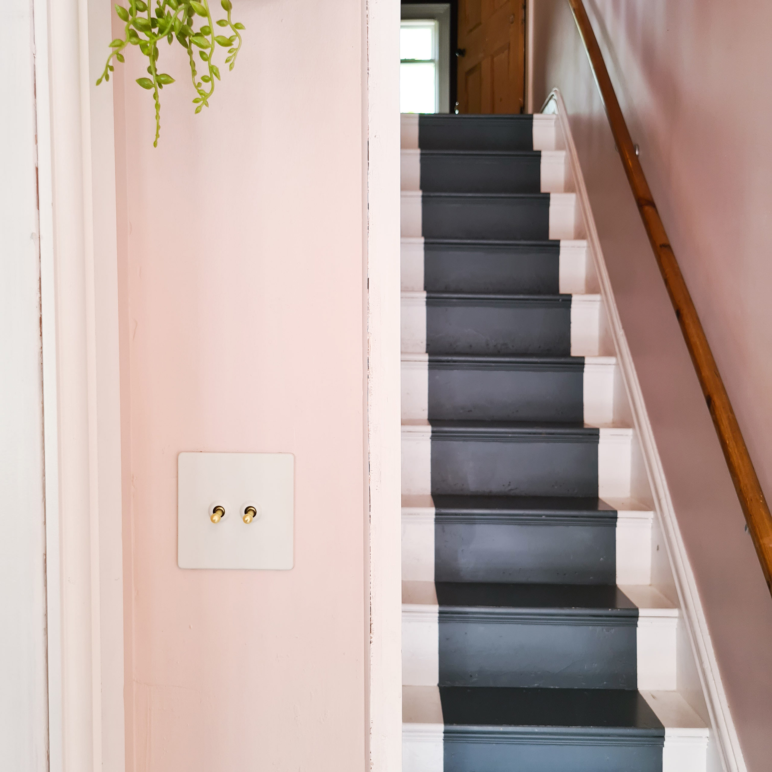 white and gold double toggle switch on soft pink wall in a hallway besides a flight of dark grey and white painted wooden stairs