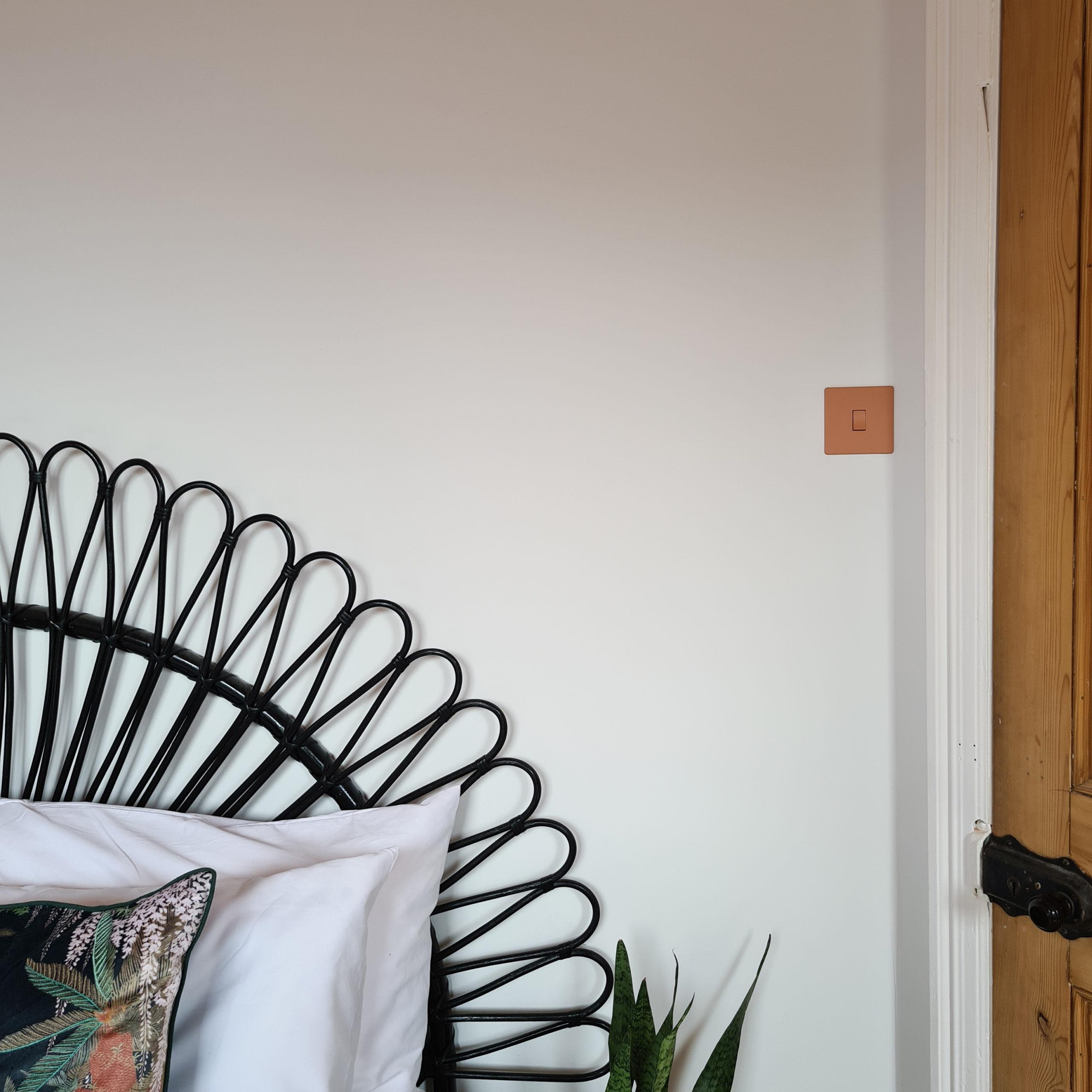 cinnamon single rocker switch on a white bedroom wall next to black rattan headboard