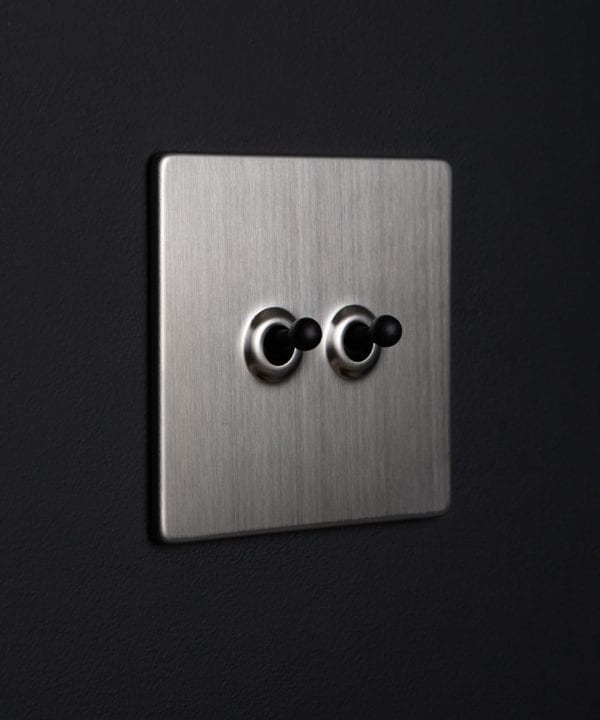 chrome toggle switch with double black toggle detail against black background