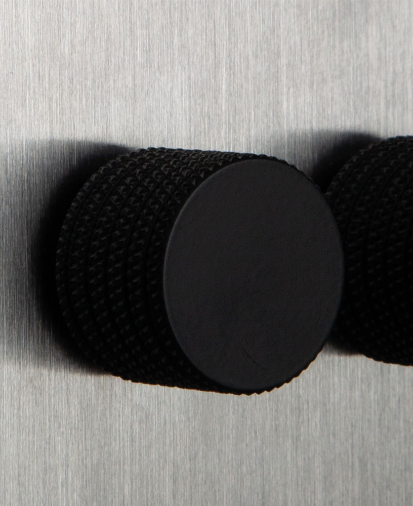 closeup of black dimmer knob on silver backplate of double dimmer switch
