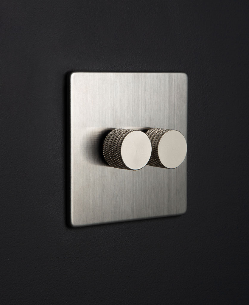 silver and silver double dimmer switch against black background