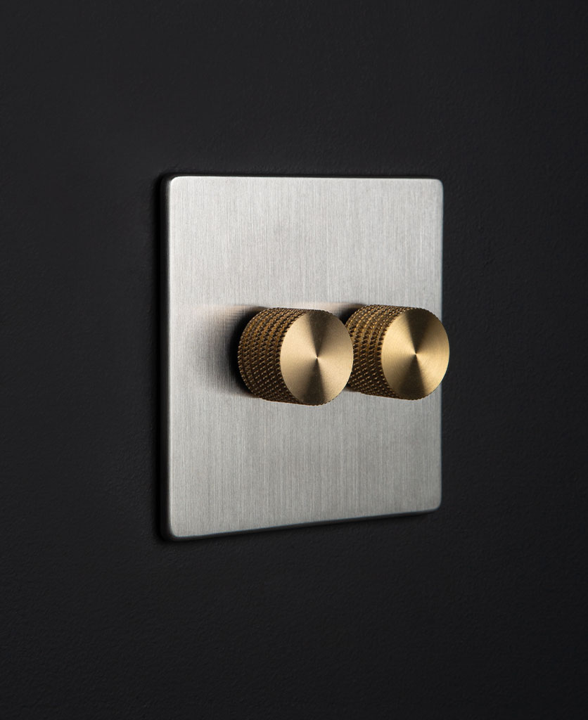 silver and gold double dimmer against black background