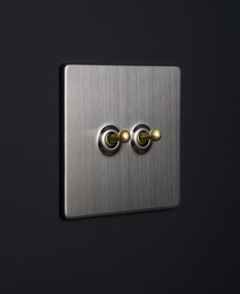 silver and gold double toggle switch against black background