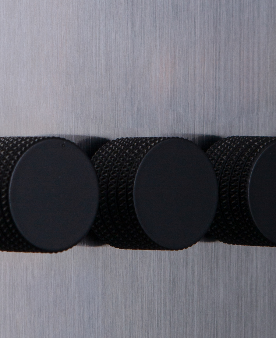 closeup of silver quadruple dimmer switch with black knurled dimming knobs