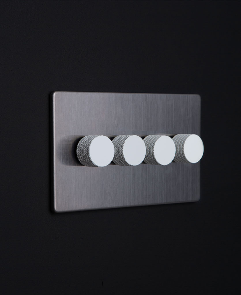 Silver wall dimmer switch with four white knurled dimming knobs on dark background