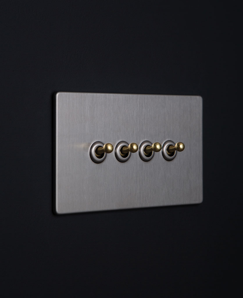 silver and gold quad toggle switch against black background