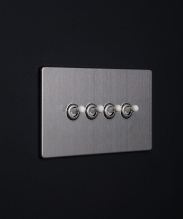 Silver metal light switches with quadruple white toggle detail against black background