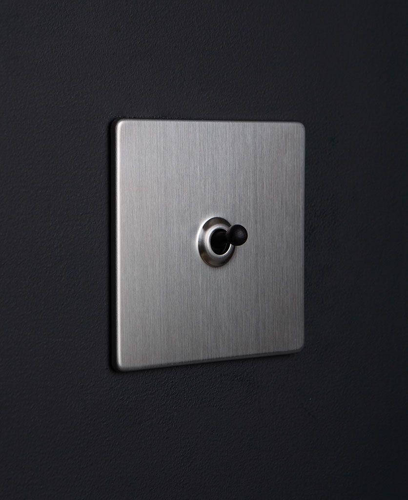 silver and black single toggle against black background