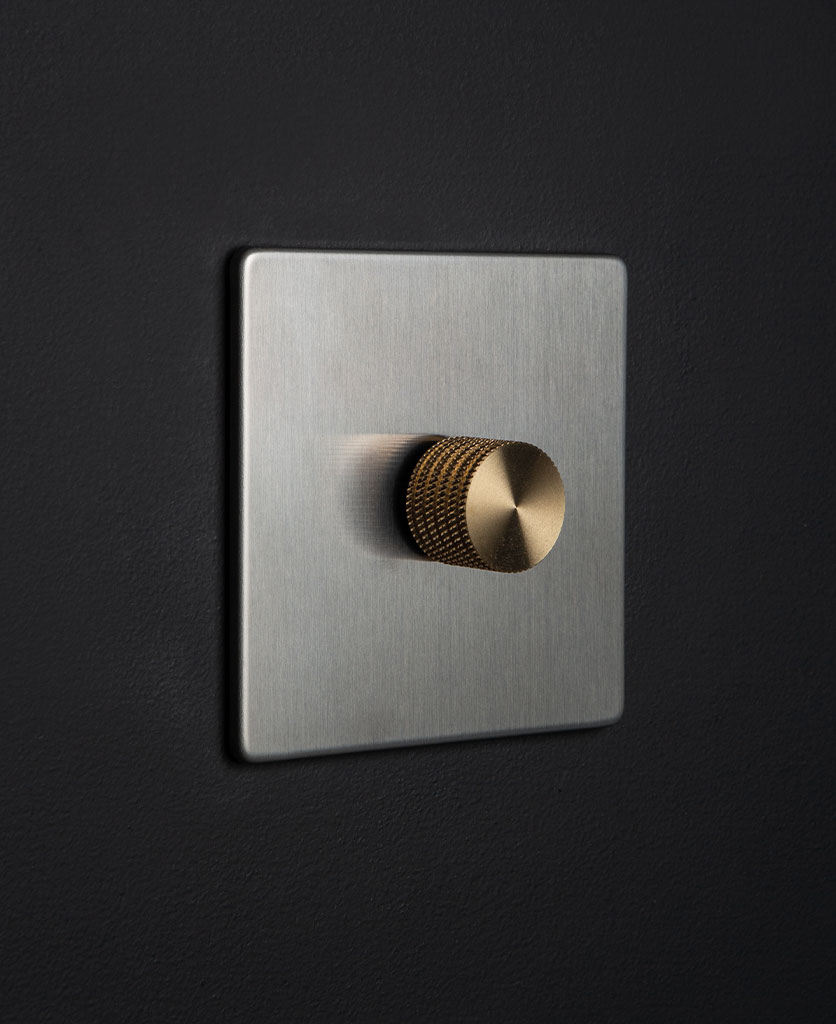 silver and gold single dimmer switch against black background
