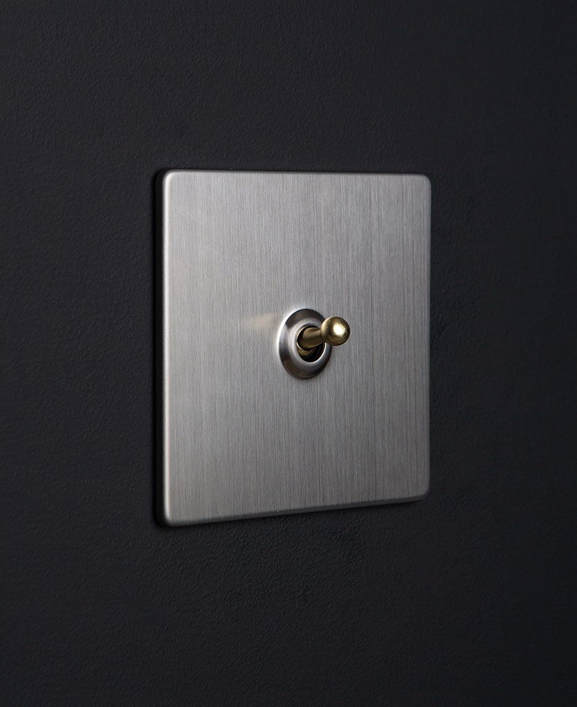 silver and gold single toggle against black background