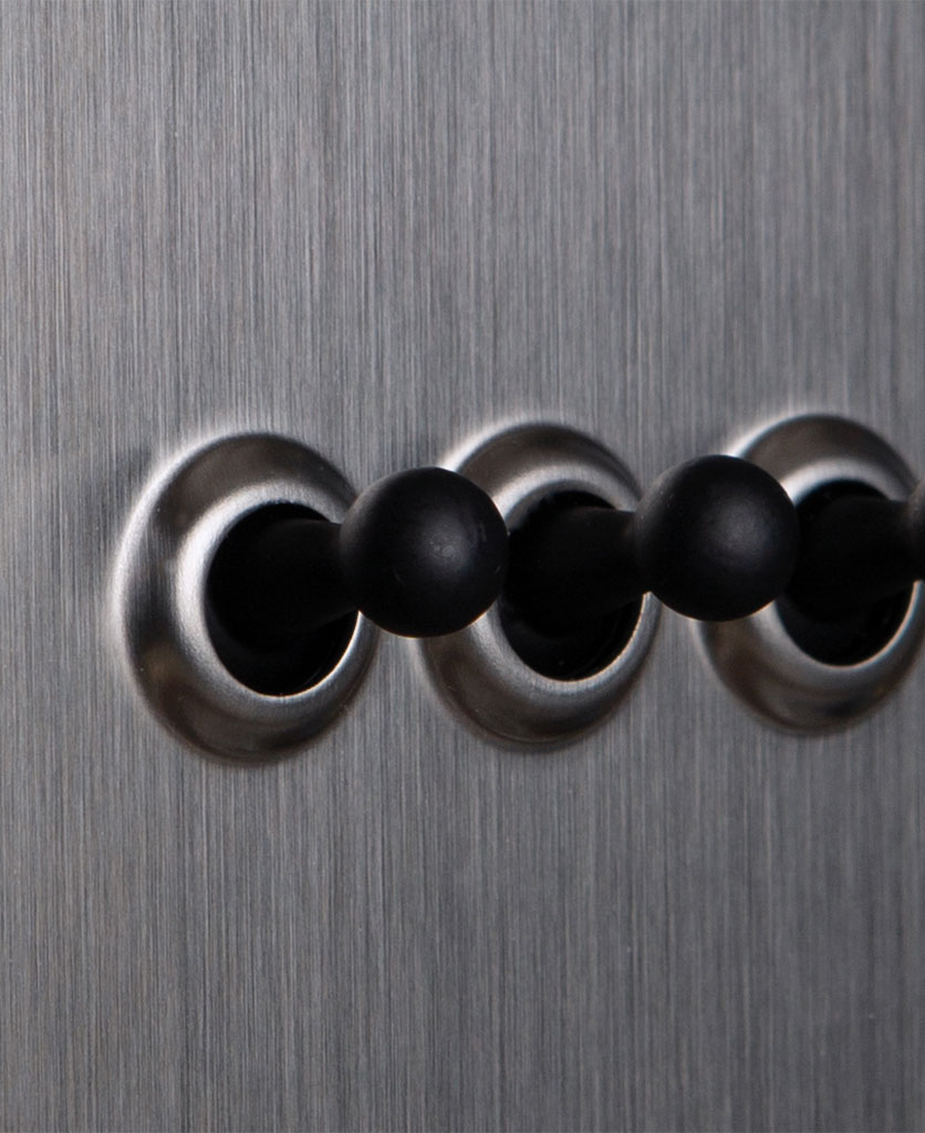 closeup of silver and black triple toggle switch