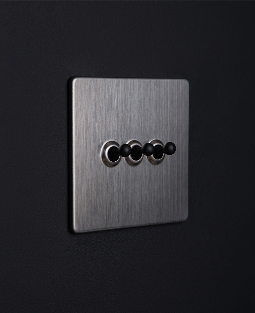 silver and black triple toggle switch against black background