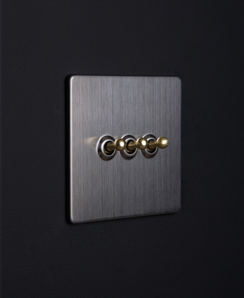 Silver metal light switch with triple gold toggle detail against black background
