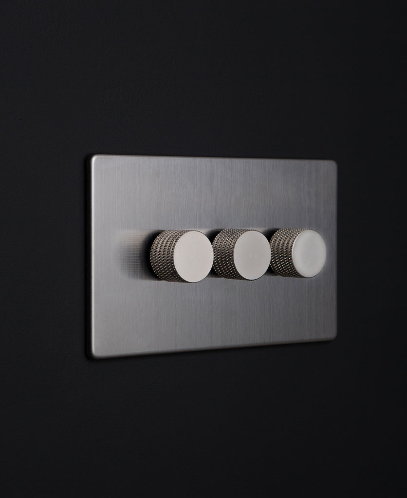silver triple dimmer switch against black background