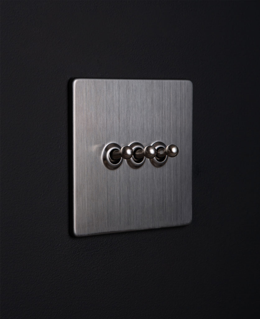 silver triple toggle switch against black background