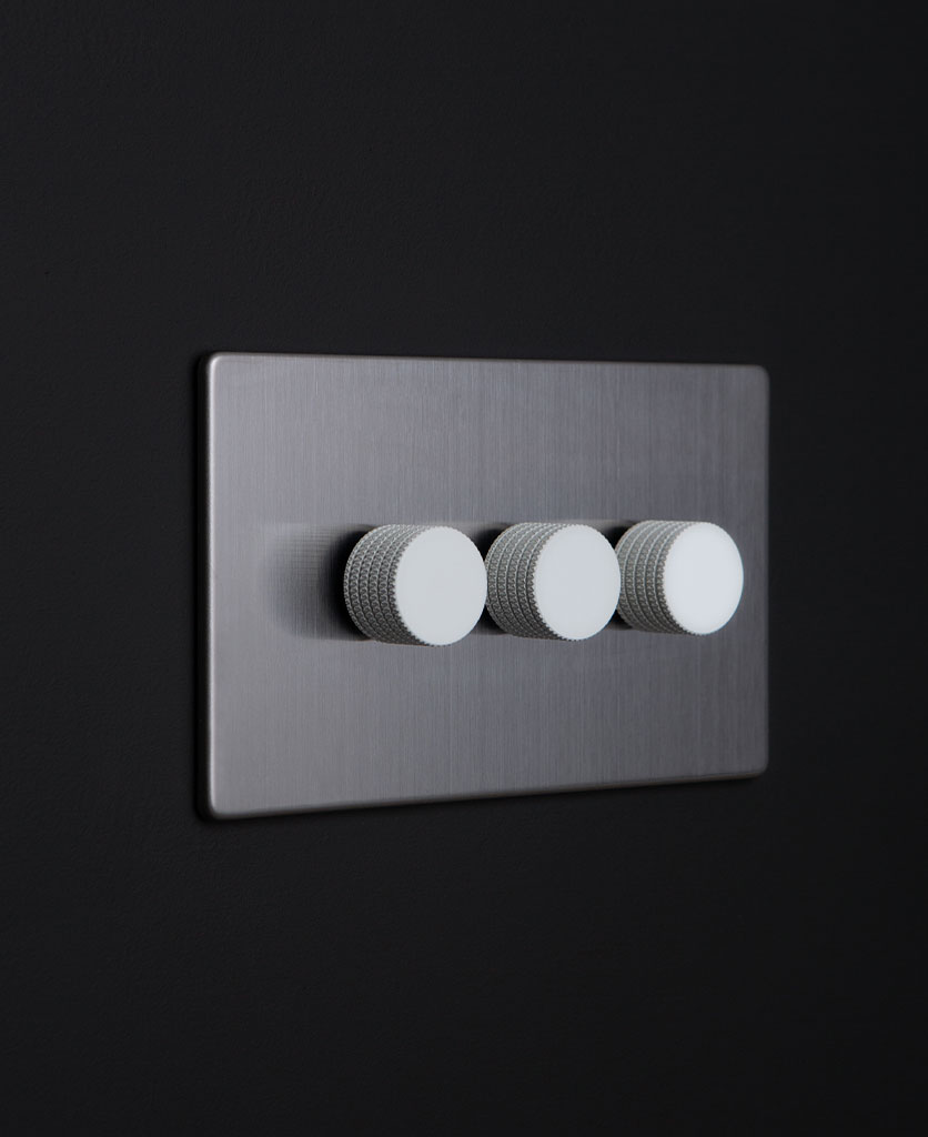 silver and white triple dimmer switch against black background