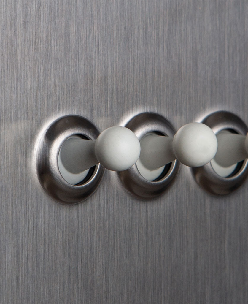 closeup of silver and white triple toggle switch