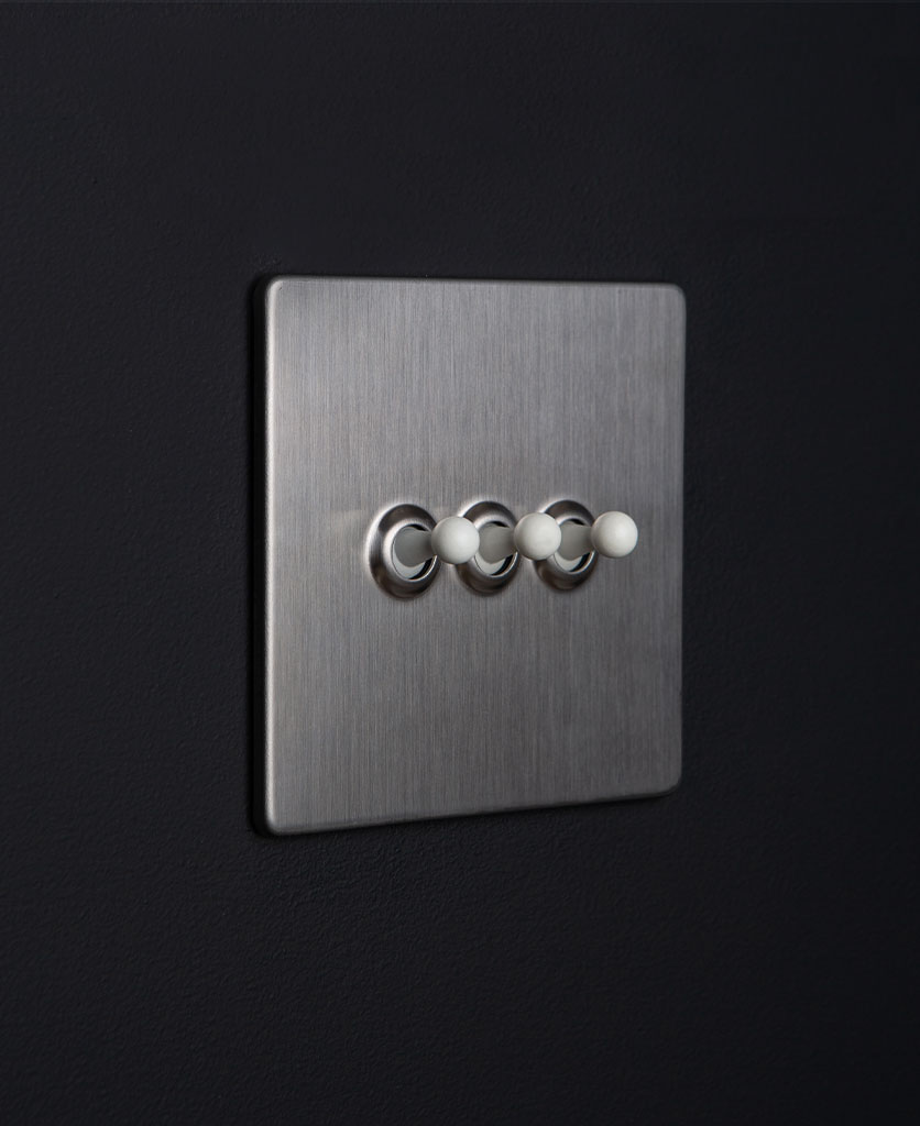 silver and white triple toggle switch against black background