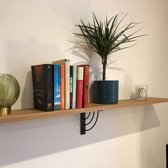 marilyn shelf bracket holding a wooden shelf with books, a candle and small potted plant