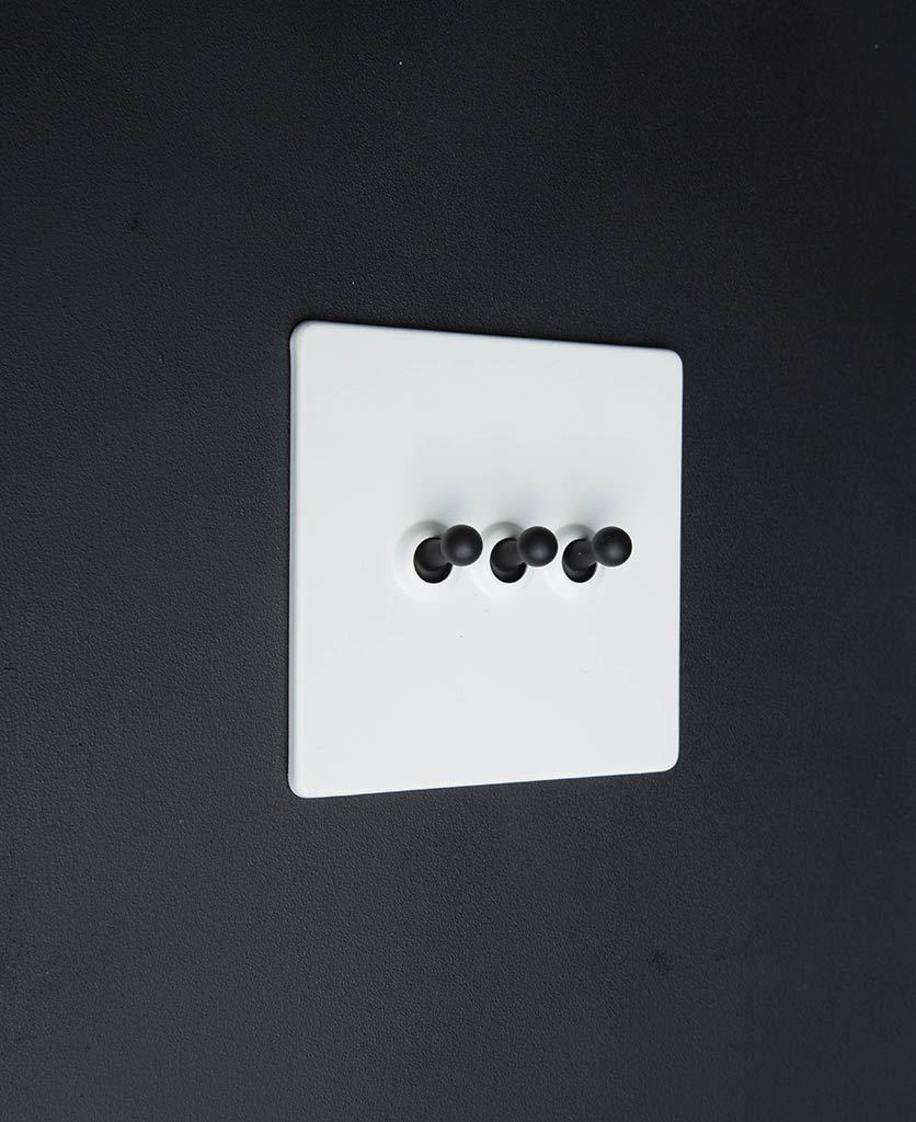 white toggle switch with triple black toggle detail against black background