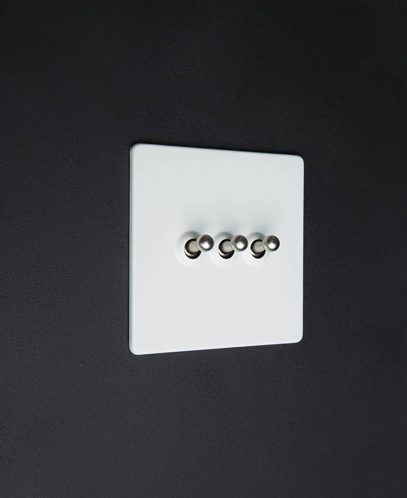 white and silver triple toggle switch against black backkground