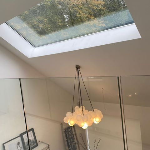 large frosted bubble chandelier ligth suspended from sloping white ceiling