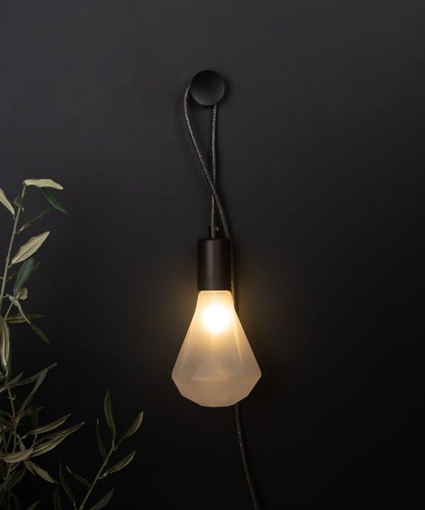 plug in wall light elle against black background