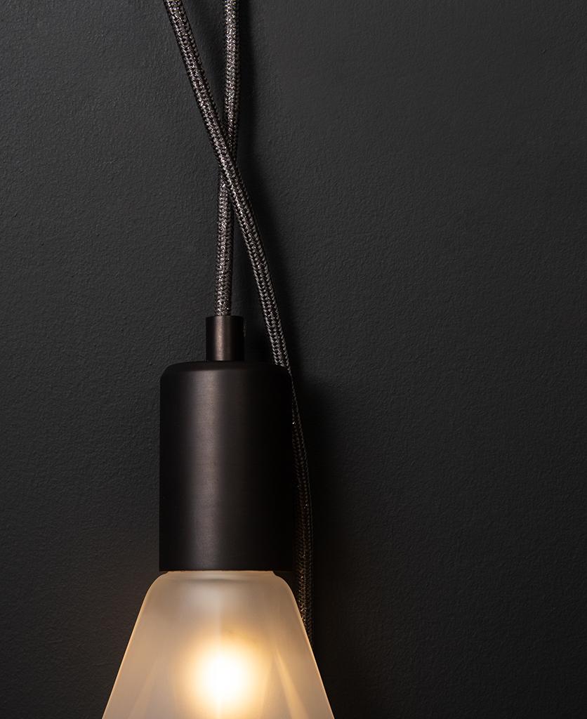 elle christalle wall lamp closeup against black background