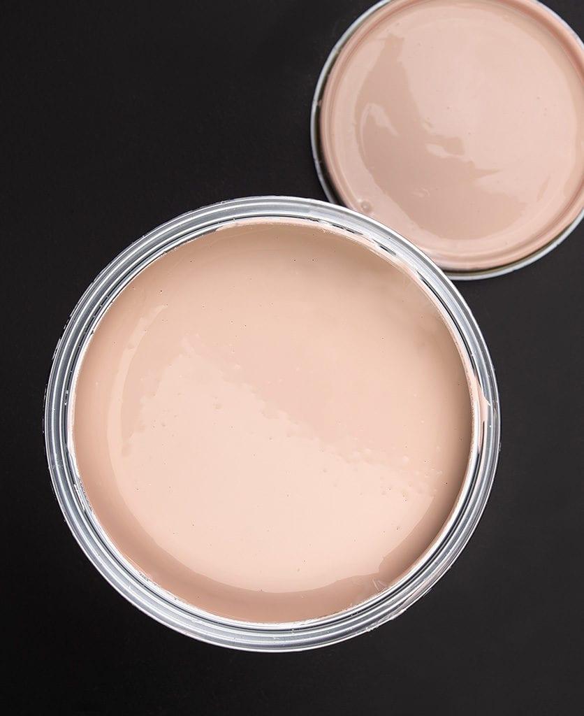 Get plastered dusky pink paint tin on dark background