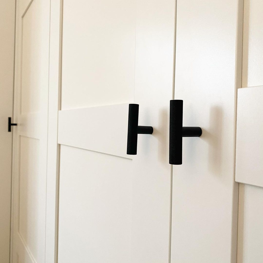 t-bar skyscraper handles in black on white panelled cupboards