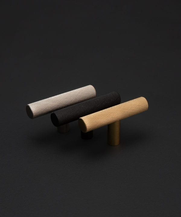 Skyscraper knurled t handle inj gold, black and silver against a black background