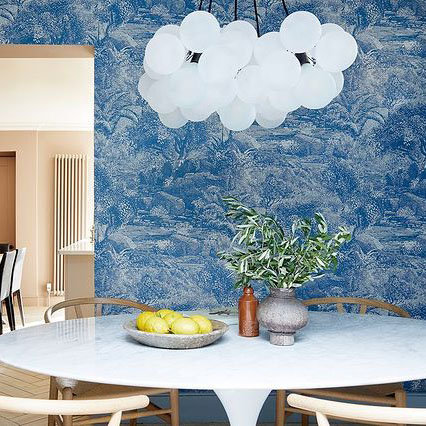 Large frosted bubble chandelier against blue and white french style wallpaper suspended above a white dining table