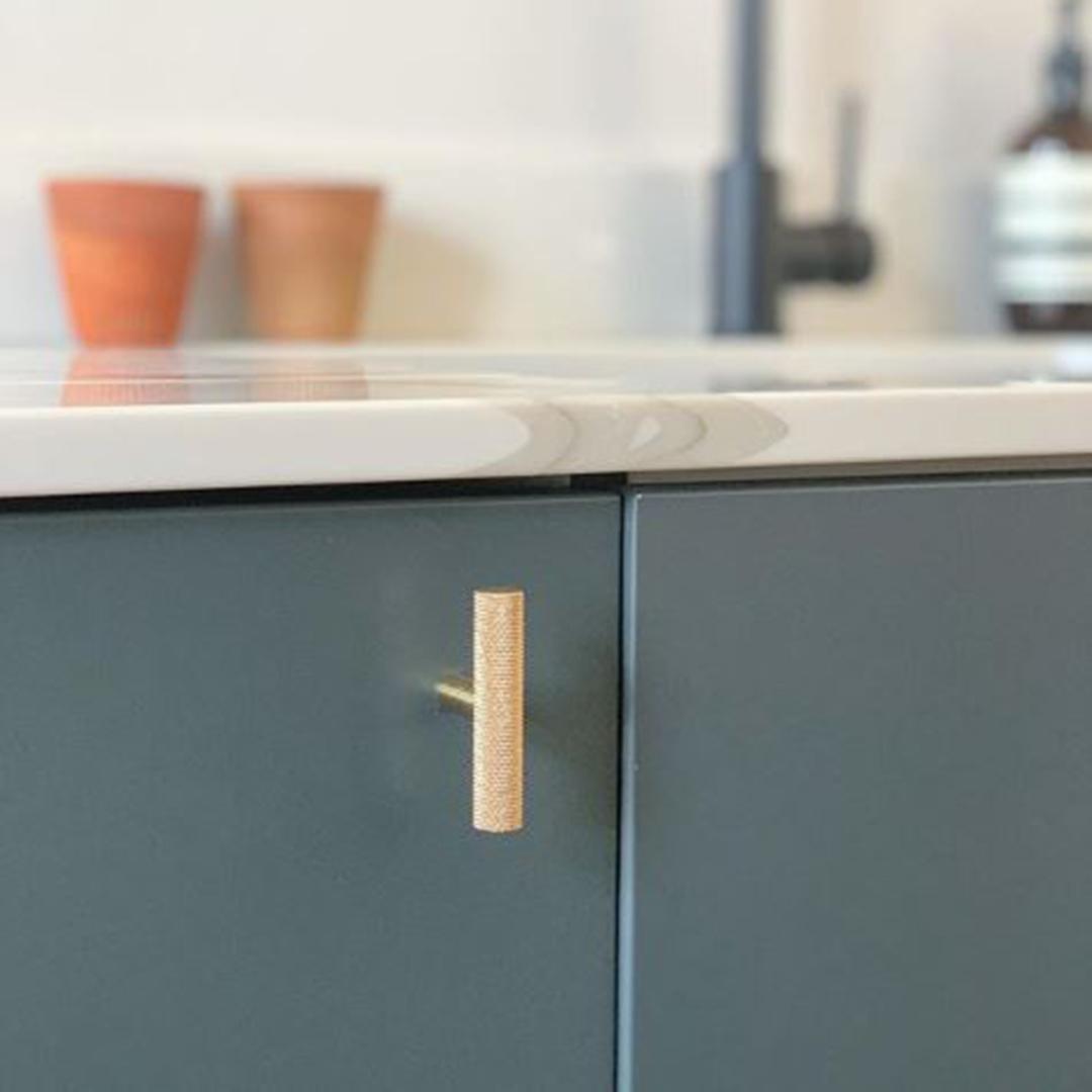 gold t-bar skyscraper handle on navy cupboard door