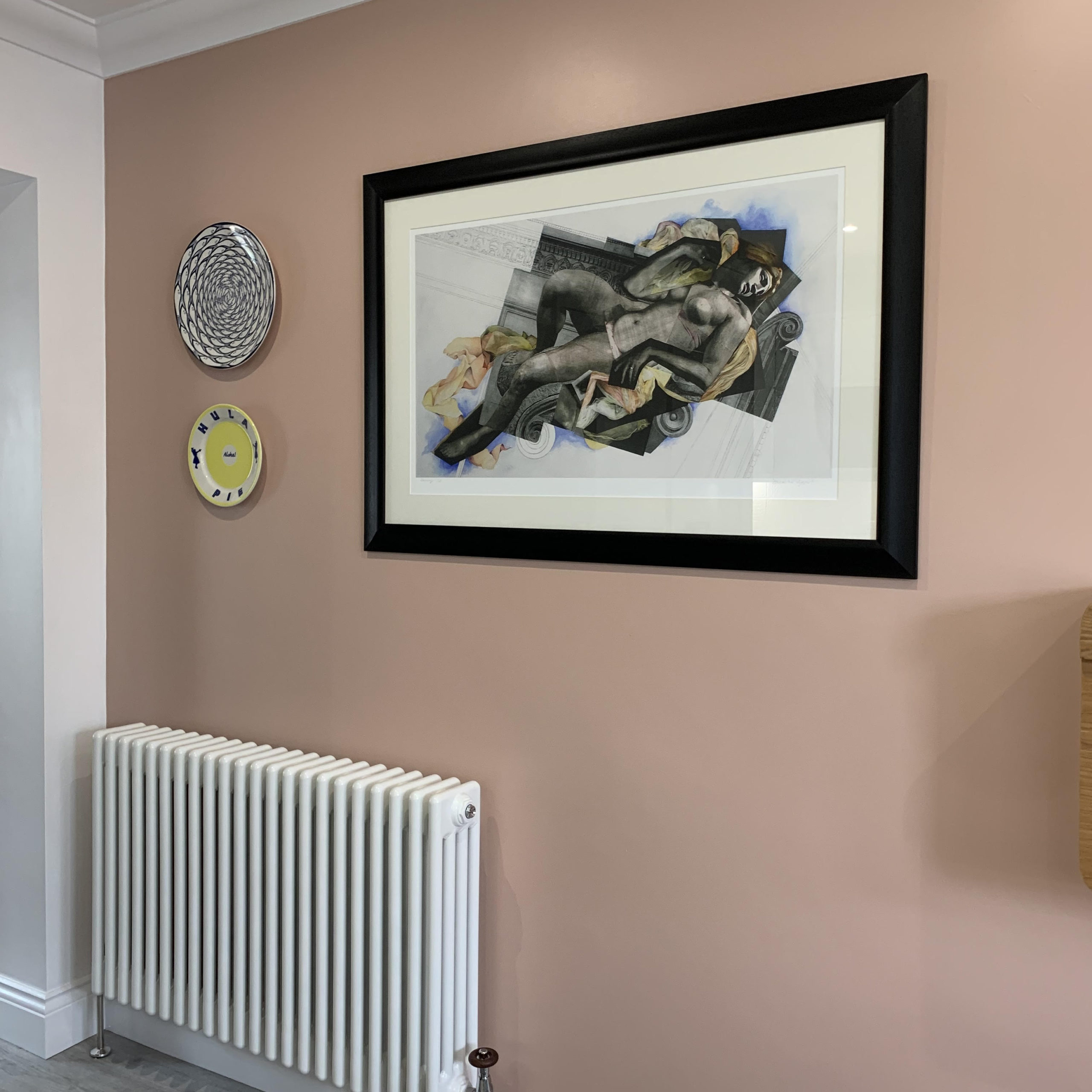 get plastered painted wall with framed artwork, hung plates and a white radiator