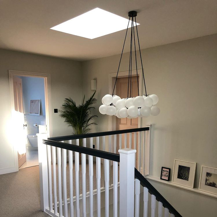 large frosted bubble chandelier suspended in a hallway above the stairs in a grey, black and white space