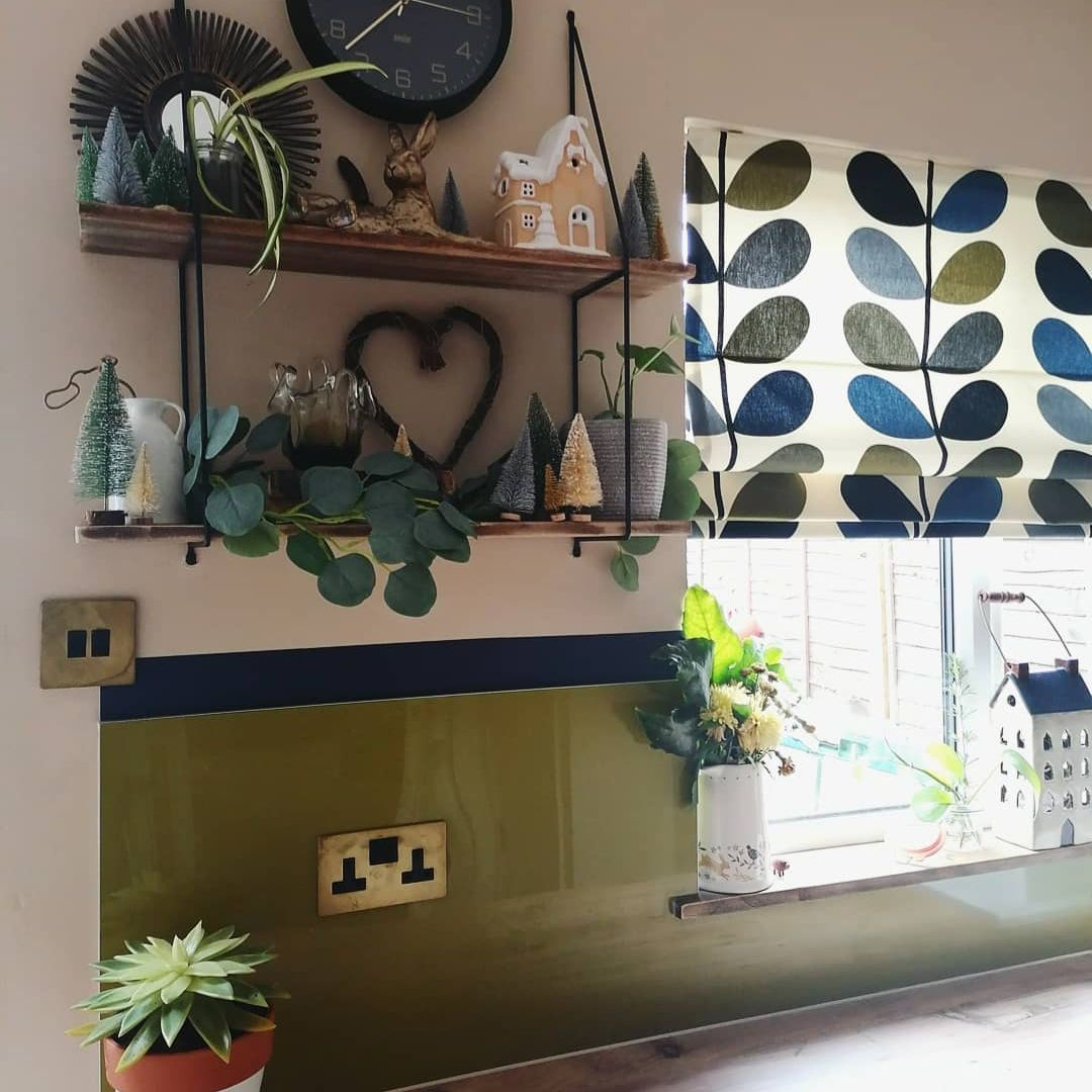 smoked gold double switch on green splashback in a kitchen