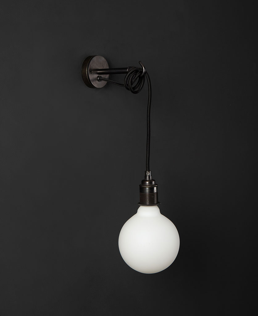 Black wall mounted light with unlit opal bulb against a black wall