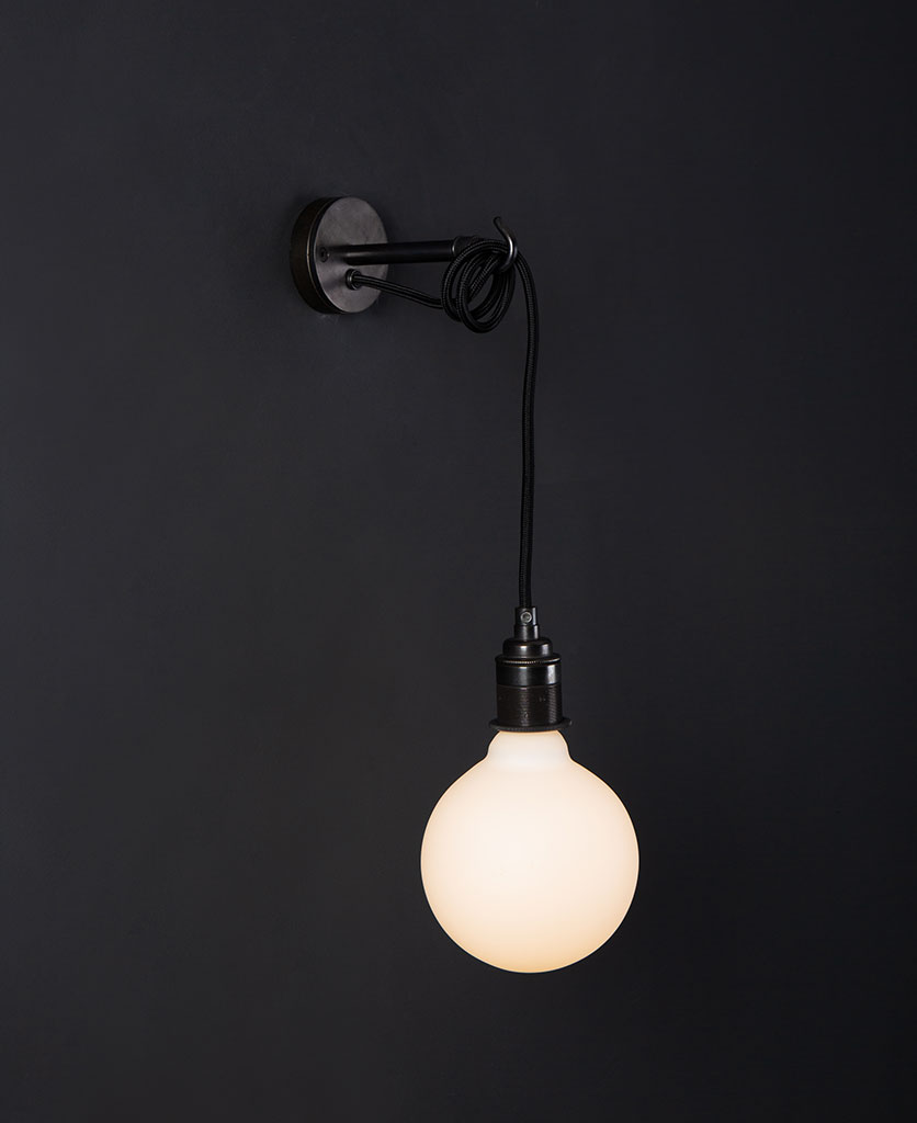 Black wall mounted light with lit opal bulb against a black wall