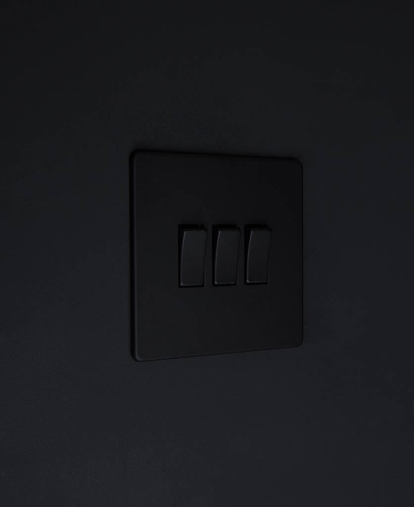 black switch 3 gang light switch with black triple rocker detailing on black wall