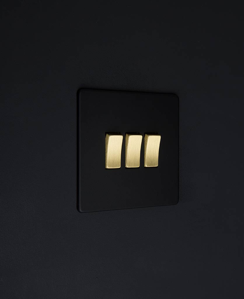 black switch 3 gang light switch with gold triple rocker detailing on black wall