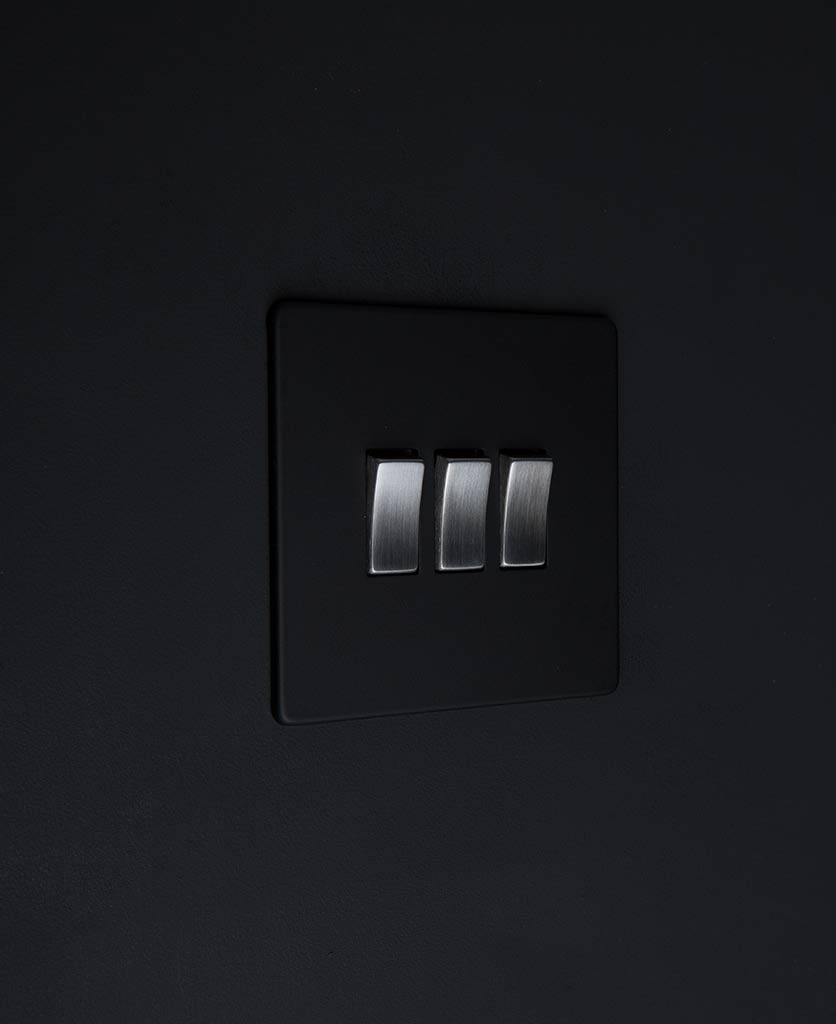 black switch 3 gang light switch with silver triple rocker detailing on black wall