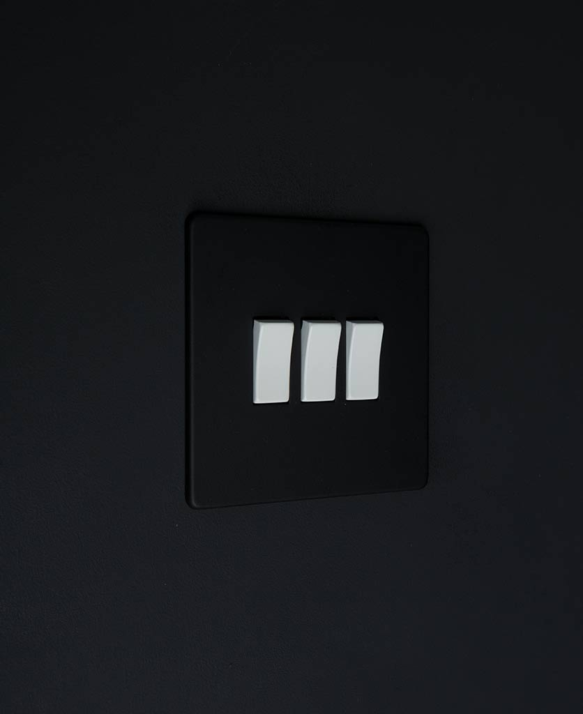 black switch 3 gang light switch with white triple rocker detailing on black wall