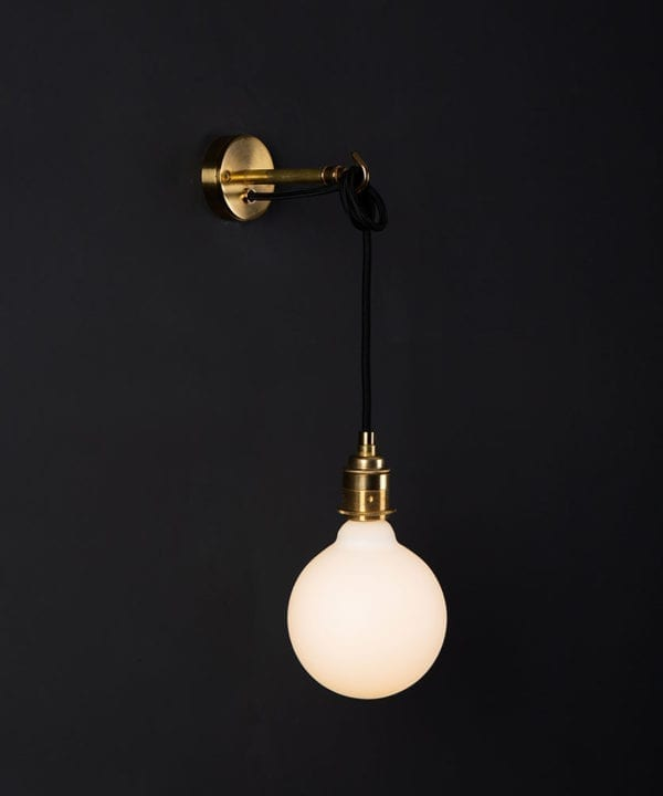Brass wall mounted light with lit opal bulb against a black wall