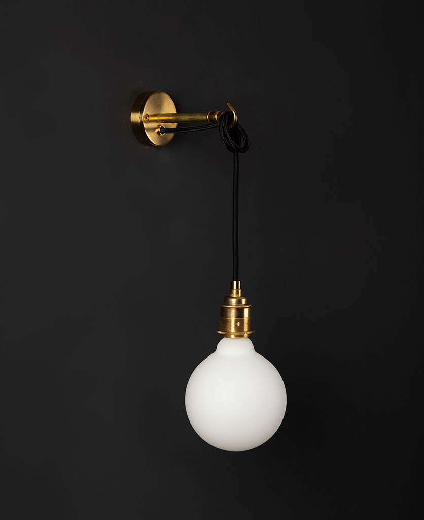 Brass wall mounted light with unlit opal bulb against a black wall